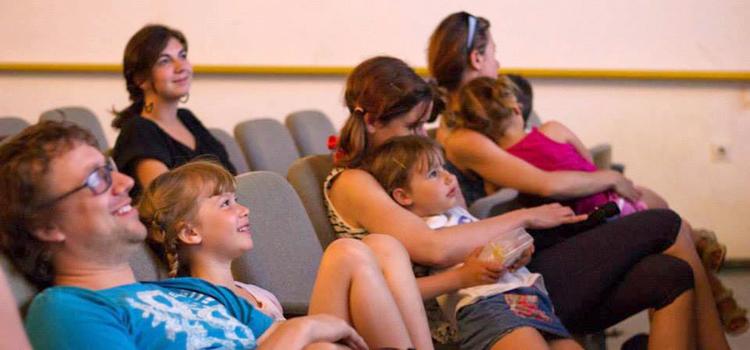 Eine Gruppe Kinder und Erwachsener in einem Kinosaal